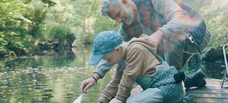 Oticon More Hörgerät Mann mit Kind am Wasser
